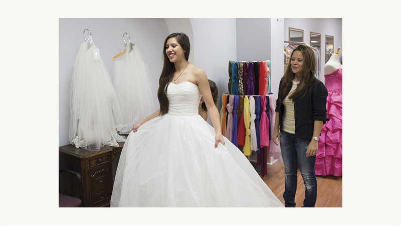 Woman trying on wedding dresses