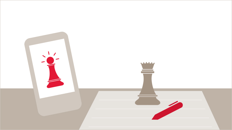 Chess pieces with paper and pen as well as a smartphone to show options for creating a budget
